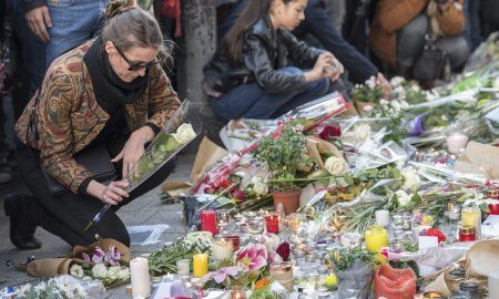 A Woman Places A Flower in Paris At The Bataclan.